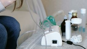 Use nebulizer and inhaler for the treatment. Closeup woman`s hands takes inhaler mask. Side view.  stock video footage
