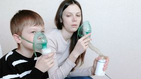 Use nebulizer and inhaler for the treatment. Woman and boy inhaling through inhaler mask. Side view. Use nebulizer and inhaler for the treatment. Woman and boy stock footage