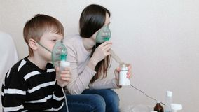 Use nebulizer and inhaler for the treatment. Woman and boy inhaling through inhaler mask. Side view. Use nebulizer and inhaler for the treatment. Woman and boy stock video footage