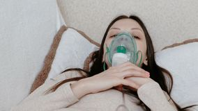 Use nebulizer and inhaler for the treatment. Young woman inhaling through inhaler mask lying on the couch. Front view. Use nebulizer and inhaler for the stock video footage