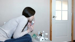 Use nebulizer and inhaler for the treatment. Young woman inhaling through inhaler mask. Side view. Young woman inhaling through inhaler mask. Side view stock video footage