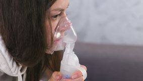 Use nebulizer and inhaler for the treatment. Young woman inhaling through inhaler mask. Close-up face, side view. Use nebulizer and inhaler for the treatment stock video
