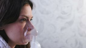 Use nebulizer and inhaler for the treatment. Young woman inhaling through inhaler mask. Close-up face, side view. Use nebulizer and inhaler for the treatment stock footage