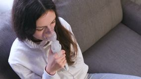 Use nebulizer and inhaler for the treatment. Young woman inhaling through inhaler mask. Use nebulizer and inhaler for the treatment. Young woman inhaling stock video footage