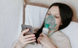 Use nebulizer and inhaler for the treatment. Young woman inhaling through inhaler mask lying on the couch and chatting. In mobile phone. Side view royalty free stock photo