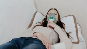 Use nebulizer and inhaler for the treatment. Young woman inhaling through inhaler mask lying on the couch. Front view. Use nebulizer and inhaler for the stock video