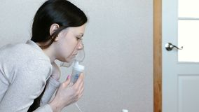 Use nebulizer and inhaler for the treatment. Young woman inhaling through inhaler mask. Side view. Use nebulizer and inhaler for the treatment. Young woman stock footage