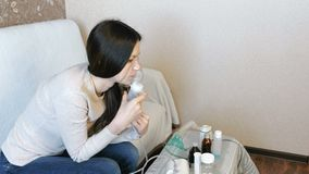 Use nebulizer and inhaler for the treatment. Young woman inhaling through inhaler mask. Side view. Use nebulizer and inhaler for the treatment. Young woman stock video footage