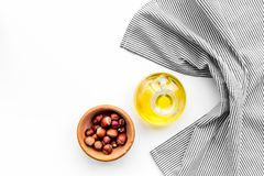 Use nut oil as cosmetics. Hazelnut oil in jar near hazelnut in bowl on white background top view copy space. Use nut oil as cosmetics. Hazelnut oil in jar near Royalty Free Stock Image