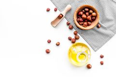 Use nut oil as cosmetics. Hazelnut oil in jar near hazelnut in bowl on white background top view copy space. Use nut oil as cosmetics. Hazelnut oil in jar near Stock Image