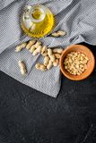 Use nut oil as cosmetics. Peanut oil in jar near peanut in bowl on blue tablecloth on black background top view copy. Use nut oil as cosmetics. Peanut oil in jar Stock Image