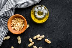 Use nut oil as cosmetics. Peanut oil in jar near peanut in bowl on black background top view copy space. Use nut oil as cosmetics. Peanut oil in jar near peanut stock photography