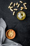 Use nut oil as cosmetics. Peanut oil in jar near peanut in bowl on black background top view copy space. Use nut oil as cosmetics. Peanut oil in jar near peanut Royalty Free Stock Images