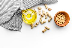 Use nut oil as cosmetics. Peanut oil in jar near peanut in bowl on blue tablecloth on white background top view copy. Use nut oil as cosmetics. Peanut oil in jar Royalty Free Stock Photography