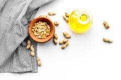 Use nut oil as cosmetics. Peanut oil in jar near peanut in bowl on blue tablecloth on white background top view copy. Use nut oil as cosmetics. Peanut oil in jar Royalty Free Stock Photo