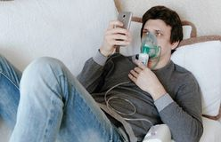 Use o nebulizer e o inalador para o tratamento Homem novo que inala através da máscara do inalador que encontra-se no sofá e que  imagens de stock