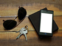 Daily use objects on a wooden table. Wallet,sunglasses,keys and smartphone on a wooden table Stock Photos