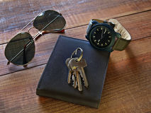Daily use objects on a wooden table. Wallet,sunglasses,keys and wristwatch on a wooden table Stock Photo