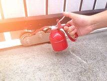 Use oiler to lubricate the door wheels. Lubricants for the rainy season stock photo