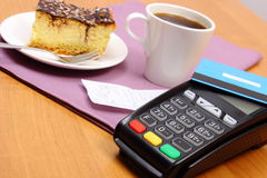 Use payment terminal for paying for cheesecake and coffee in cafe, finance concept Royalty Free Stock Photo