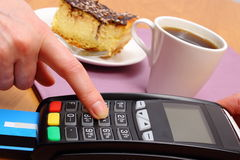 Use payment terminal for paying for cheesecake and coffee in cafe, finance concept Royalty Free Stock Photography