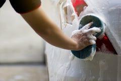 Use seu assistente para travar a esponja e para lustrar a janela de carro fotografia de stock royalty free