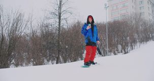 Use seu smartphone para tomar imagens das paisagens quando snowboarding na inclinação do esqui vídeos de arquivo