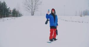 Use seu smartphone para tomar imagens das paisagens quando snowboarding na inclinação do esqui video estoque