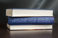 Use social media to promote your business. Book concept. Books on a table and one with  Use social media to promote your business.  cover. Book concept Stock Image