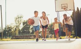 Use the summer in a healthy way. Family playing basketball royalty free stock photography