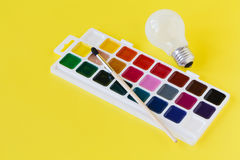 Use watercolor paints box on yellow background Royalty Free Stock Images