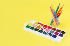 Use watercolor paints box on yellow background Royalty Free Stock Photography