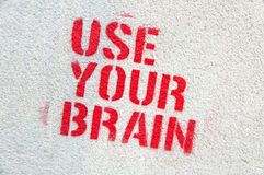 Use Your Brain graffiti. On a grey wall Stock Image
