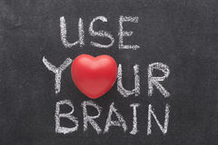 Use your brain. Phrase handwritten on chalkboard with heart symbol instead of O Stock Image