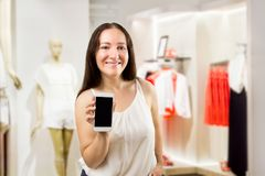 Use your phone at the store. Portrait of cheerful saleslady holding and showing the smartphone at the boutique Stock Image