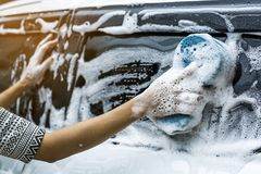 Use your right hand to catch the sponge and polish the car window. Stock Photography