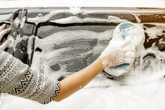 Use your right hand to catch the sponge and polish the car window. stock images