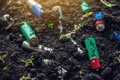Used alkaline batteries lie in the soil where plants grow. Concept of environmental pollution with toxic household waste. Used alkaline batteries lie in the soil stock photo