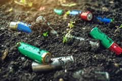 Used alkaline batteries lie in the soil where plants grow. Concept of environmental pollution with toxic household waste. Used alkaline batteries lie in the soil stock photos