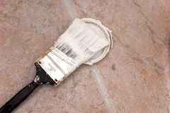 Used angled paint brush. A trim paint brush covered with paint is resting on paint covered cap on floor Royalty Free Stock Images