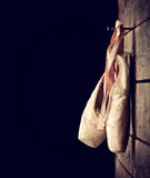 Used ballet shoes hanging on wooden background Royalty Free Stock Images