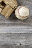Used baseball and weathered mitt on old wood Stock Image
