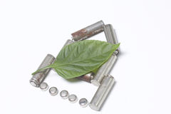 The used batteries lie in the form of a house. They are lined with a juicy green leaf. Stock Photos