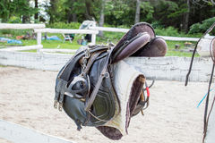 Used black dressage horse riding saddle with girth, stirrup and riding gloves Royalty Free Stock Images