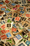 Used British Postage Stamps Background. Pile of second-hand British postage stamps used for mailing letters and parcels Royalty Free Stock Images