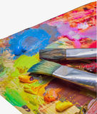 Used brushes on an artist's palette of colorful oil paint stock image