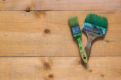 Used brushes on raw wood board surface. Flat view from top Royalty Free Stock Images