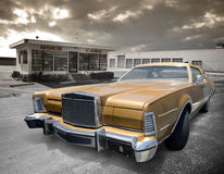 Used car. A golden vintage lincoln on a used car lot with garage bays in the background Royalty Free Stock Photos