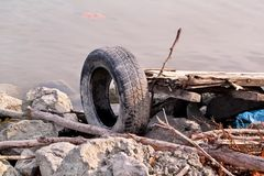 Used car tire left in nature. Old used car tyre left tossed by cost of water. The problem of trash on the beach river caused by man-made pollution and Stock Photo