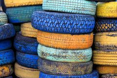 Car tires painted in different colors are stacked on top of each other. Used car tires with different protectors painted in different colors folded one on stock photos
